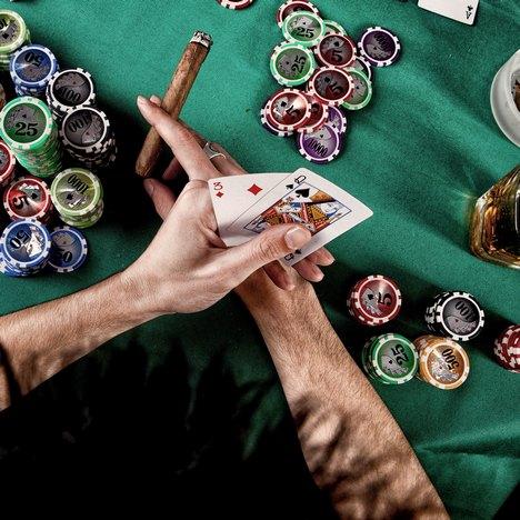 gicatore con sigaro al tavolo da poker.